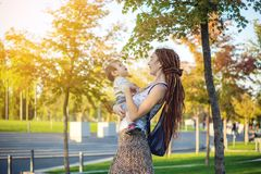 有走在晴朗的公园的小儿子的现代愉快的妈妈 母性和秋天心情喜悦  库存照片