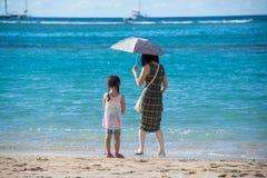有走在沙滩的伞和小女孩孩子的母亲在海洋 免版税图库摄影