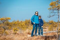 有走在沼泽, Kemeri国家公园,拉脱维亚的足迹的母亲的逗人喜爱的小男孩 库存照片