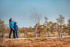 有走在沼泽, Kemeri国家公园,拉脱维亚的足迹的母亲的逗人喜爱的小男孩 免版税库存照片