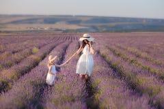 有走在淡紫色领域的可爱的女儿的年轻美丽的夫人母亲在美妙的礼服和帽子的一周末天 免版税库存图片