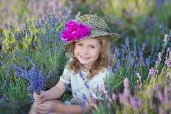 有走在淡紫色领域的可爱的女儿的年轻美丽的夫人母亲在美妙的礼服和帽子的一周末天 库存图片