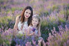 有走在淡紫色领域的可爱的女儿的年轻美丽的夫人母亲在美妙的礼服和帽子的一周末天 免版税库存照片