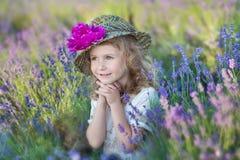 有走在淡紫色领域的可爱的女儿的年轻美丽的夫人母亲在美妙的礼服和帽子的一周末天 库存照片