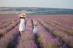 有走在淡紫色领域的可爱的女儿的年轻美丽的夫人母亲在美妙的礼服和帽子的一周末天 免版税图库摄影