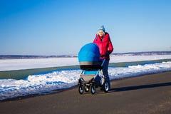 有走在温特帕克的婴儿车的母亲 免版税库存照片