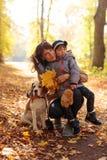 有走在autum的小女孩和小猎犬的中间年龄妇女 免版税库存图片
