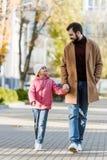 有走外面在秋天成套装备和看彼此的小女儿的快乐的父亲 库存照片