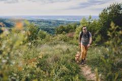 有走沿一条供徒步旅行的小道的狗的人 免版税库存图片