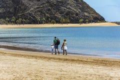有走沿离开的海滩ne的妇女和孩子的一个人 免版税库存图片