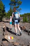 有走沿路线的一个小女孩的白种人妇女穿过Teno山的森林  对月球土地的足迹 免版税库存照片