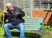 有走的藤茎或棍子挥动的老人 免版税库存照片