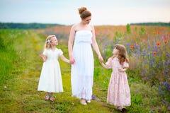 有走通过夏天领域的两个小女孩的美丽的母亲 免版税库存图片