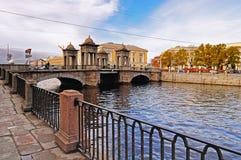 有走Fontanka河的人和堤防的老Kalinkin桥梁在圣彼德堡,俄罗斯 图库摄影