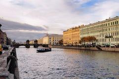 有走Fontanka河的人和堤防的老Kalinkin桥梁在圣彼德堡,俄罗斯 免版税库存图片