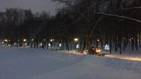 有起动的车灯的小雪去除的拖拉机清洗小径在城市公园在落的雪下 影视素材