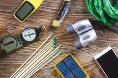 有起动的远足或旅行设备,指南针,双筒望远镜,在木背景的比赛 有效的生活方式概念 免版税库存图片