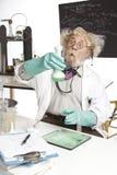 有起泡沫的烧杯的惊奇高级科学家 库存照片