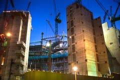 有起重机的建筑工地在伦敦市事务 在英国银行的新发展计划旁边 被停泊的晚上端口船视图 免版税库存图片
