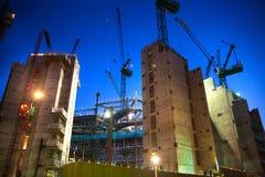 有起重机的建筑工地在伦敦市事务 在英国银行的新发展计划旁边 被停泊的晚上端口船视图 免版税库存照片