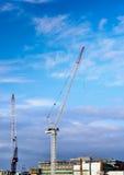 有起重机的建造场所反对蓝天 免版税库存图片