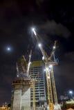 有起重机的建造场所在夜低角度垂直 免版税图库摄影