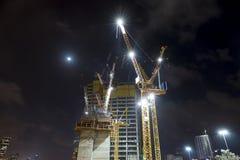 有起重机的建造场所在夜低角度 库存图片