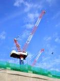 有起重机的建造场所在蓝天背景 免版税库存照片