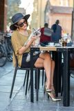 有超短裙的一名典雅的意大利妇女拿着在她的胳膊的一只猫 库存照片