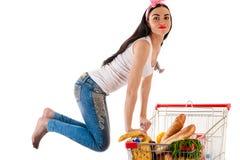 有超级市场台车的美丽的妇女 免版税库存照片