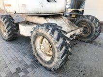 有越野建筑器材踩和轮胎的,拖拉机,汽车强有力的重要人物 库存照片