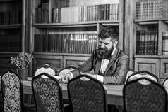 有趣的书概念 愉快的人在内部的葡萄酒坐并且享受松弛读书 正式成套装备的有胡子的人 库存照片