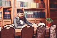 有趣的书概念 愉快的人在内部的葡萄酒坐并且享受松弛读书 正式成套装备的有胡子的人 免版税图库摄影