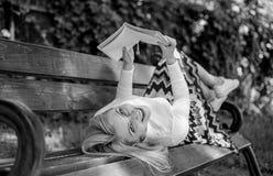 有趣的书 夫人微笑的面孔享用读户外,当放松在长凳时的休息女孩 女孩位置长凳公园 库存照片