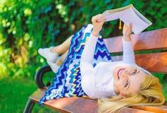 有趣的书 妇女花费与书的休闲 夫人笑容享受休息女孩读书户外,当放松时 免版税图库摄影