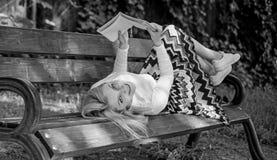 有趣的书 聪明和相当 聪明夫人放松 女孩放置放松与书,绿色自然背景的长凳公园 免版税库存照片