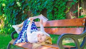有趣的书 聪明和相当 聪明夫人放松 读户外,当放松在长凳时的女孩 女孩位置长凳 免版税库存图片