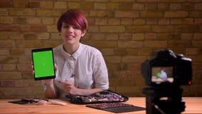 有趣的是显示片剂的绿色屏幕短发女性秀丽博客作者入照相机bricken墙壁背景 影视素材