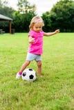 有足球橄榄球球的小女孩 库存照片