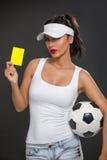有足球的性感的女孩 免版税图库摄影