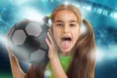有足球的滑稽的女孩显示tonque 图库摄影