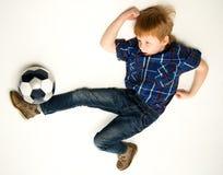 有足球的红头发人男孩 免版税库存图片