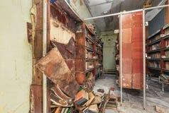 有跌下的书橱架子和腐烂的书 库存照片