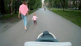 有跑在夏天公园的小女孩的愉快的年轻母亲 从一个父亲的眼睛的看法有摇篮车的 股票录像