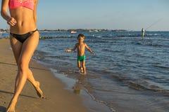 有跑在夏天海滩的母亲的愉快的小男孩 正面人的情感,感觉,喜悦 做假期的滑稽的逗人喜爱的孩子  库存照片