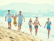 有跑在海滩的四个孩子的笑的家庭 免版税库存照片