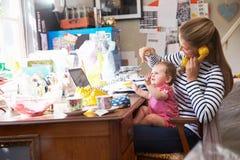 有跑小企业的女儿的母亲从内政部 免版税库存照片
