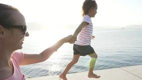 有跑小的女儿的年轻母亲举行手,微笑和笑 股票视频