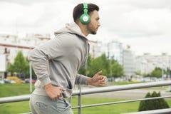 有跑步的耳机的年轻人户外 免版税库存照片