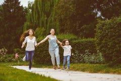 有跑的女儿和的儿子的愉快的母亲  免版税库存图片
